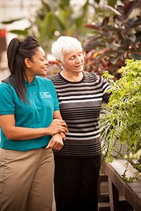 Carer and older lady in greenhouse